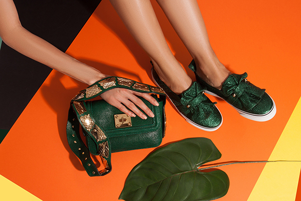 Young woman feet in green snake leathure flat slip-on