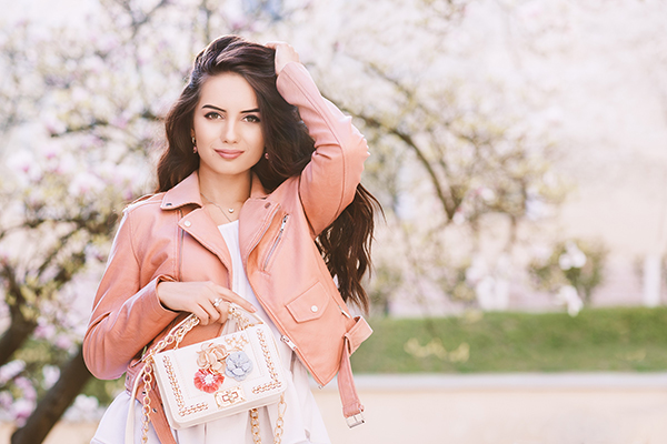 Outdoor portrait of young beautiful fashionable lady holding whi